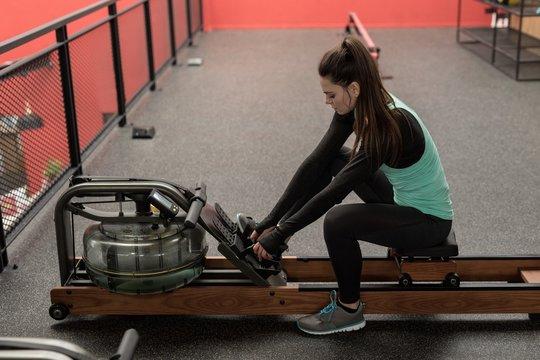Woman using rowing machine in fitness studio