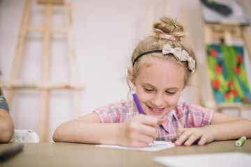 Blonde cute smiling seven-year-old girl, draws at the table in the creative studio