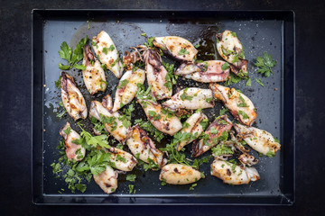 Traditional barbecue Greek calamari with herb and spices as top view on a black metal sheet