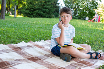 Boy with a telephone and book in hands, sits outdoors.