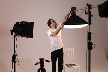 Male photographer adjusting strobe lights
