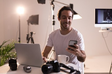Male photographer using mobile phone while working on laptop