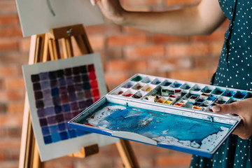 art painting hobby. creative leisure. painter holding a watercolor mixing palette. artist tools and instruments concept.