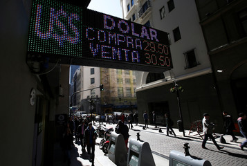People walk past an electronic board showing currency exchange rates, in Buenos Aires' financial district