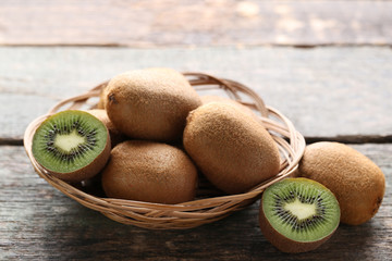 Kiwi fruits in basket on wooden table