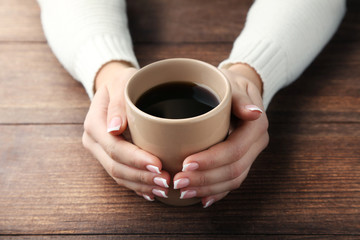 Female hands holding cup of coffee on wooden table