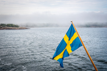 Beautiful nordic archipelago summer view  of land and island against sea and hazy horizon with Swedish flag in the foreground.
