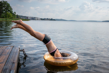 Side view of one young girl diving into water and svim ring from a jetty at a summer lake.
