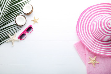 Summer accessories with coconuts and palm leaf on wooden table