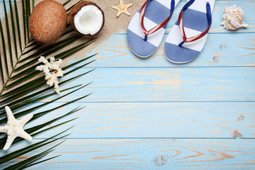 Coconuts with seashells and flip flops on wooden table