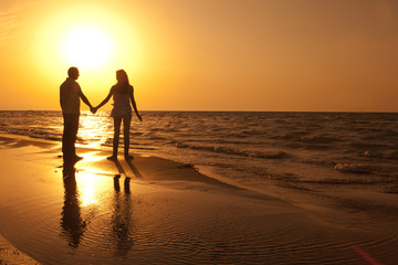 Love couple silhouette walking in the beach in summer sunset