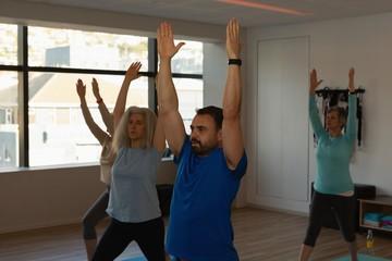 Trainer assisting senior women in performing yoga