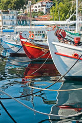Colorful fishing boats and their reflections in a water of Skiathos harbor, island of Skiathos, Greece