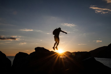 Man jumping on cliffs in sunset