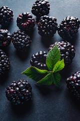 BlackBerry on a dark background with a green leaf