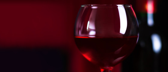 Wine. A glass and a bottle of red wine.. Red wine on a dark background.