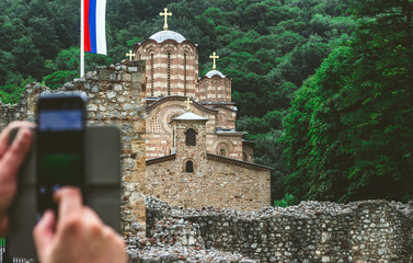 Man taking a photo of a Serbian ortodox monastery Ravanica, built in 14th century