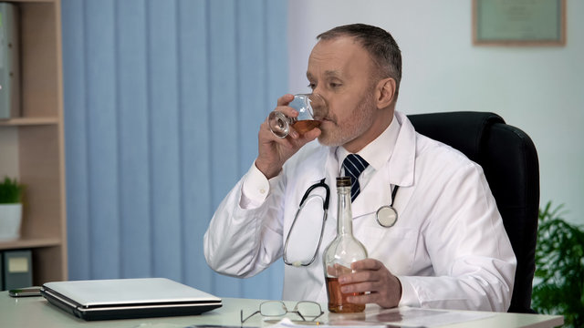 Irresponsible doctor drinking alcohol to relax at work, stressful occupation