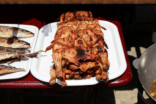 flattened and grilled chicken cooked entirely on an open fire on the embankment near the Black Sea on the grill. Reportage shooting. Republic of Crimea