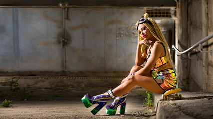 Beautiful young woman with skateboard, dressed in futuristic sexy clothes