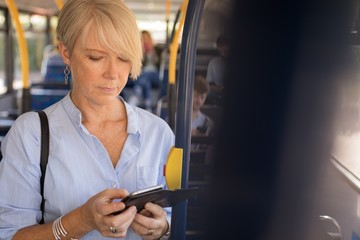 Female commuter using mobile phone while travelling in bus