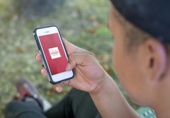 User on Smartphone in Park Mockup