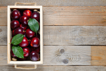 Plums in box on wooden table