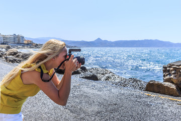 Woman photographer Nature photographer shooting the sea. Travel Concept.