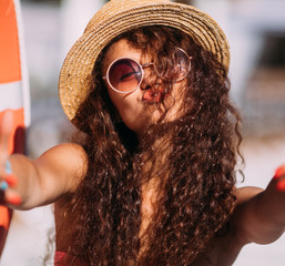 Close up portrait Nice laughing girl in hat making selfie on the beach.Cute summer fashion portrait of beauty long curly dark hair woman having fun