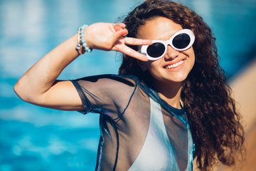 Positive summertime portrait of stylish girl having fun near pool, trendy outfit and sunglasses, traveling vibes, amazing view on luxury pool.Sexy perfect fit body woman. Copy, empty space for text