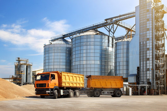 Agricultural silo truck of orange color on the territory of grain storage in sunny weather.