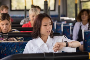 Female commuter checking time while travelling in modern bus