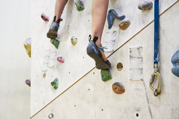 Woman training on a climbing wall in sport hall, close-up of shoes, ready to workout