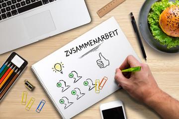 Hand skizziert Ideen-Prozess auf Papier und hebt Zusammenarbeit hervor