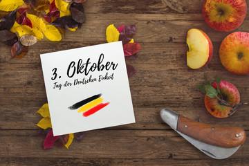 """Herbstlaub, Äpfel und Karton mit Aufschrift """"3. Oktober - Tag der Deutschen Einheit"""""""