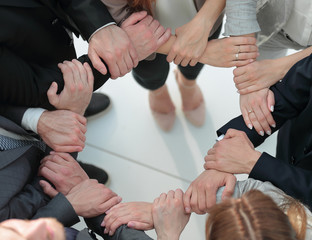 group of employees forming a circle out of hands