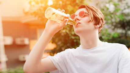 Young man in red glasses drinks beer with pleasure. Outdoor