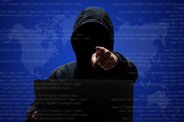 Male hacker with dark face in hoodie, stands in front of laptop computer, points at camera, steals data, downloads private information, poses against digital interface background. Cyberspace.