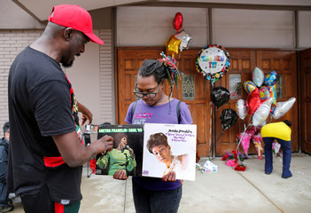 Mourners look at album covers of singer Aretha Franklin outside the New Bethel Baptist church in Detroit