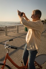 Senior man taking pictures near sea side at promenade