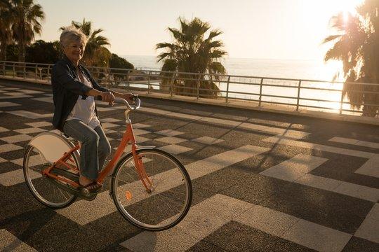 Senior woman riding bicycle at promenade