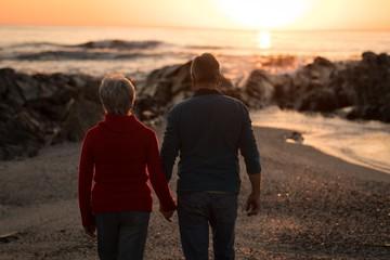 Senior couple walking on beach during sunset