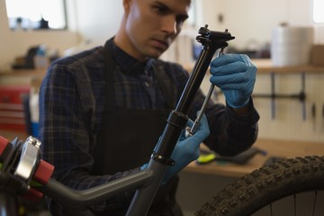 Man repairing bicycle seat in workshop