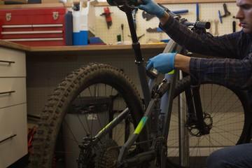 Man adjusting bicycle seat with spanner in workshop