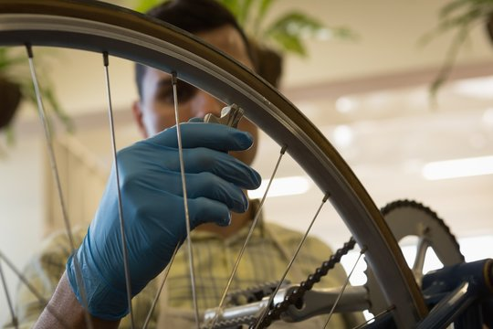 Man fixing bicycle wheel strings in workshop