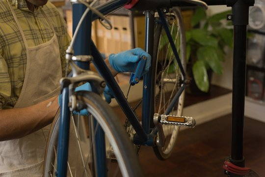 Mechanic fixing bicycle brake wire in workshop
