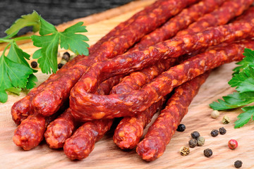 Sausages with peppercorns and parsley on cutting board
