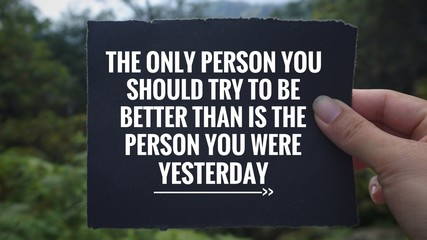 Inspirational and motivational quote - 'The only person you should try to be better than is the person you were yesterday' written on a black paper. Vintage styled blurry background.