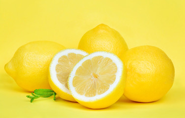 Fresh lemons with mint on yellow background
