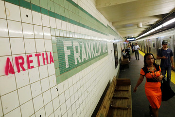 """""""Aretha"""" is spray painted next to a sign at the Franklin Street subway station in the Brooklyn borough of New York"""